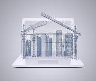 Torenkraan en wolkenkrabbers op laptop stock afbeeldingen