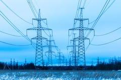 Torens van elektrische leiding op het gebied van het de winterplatteland op de achtergrond van blauwe hemel en het bos met de dra royalty-vrije stock fotografie