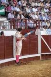 Torero español Juan Jose Padilla que salta y suspendido en el aire con dos banderillas en la mano derecha que mira el toro Imagen de archivo