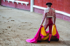 Torero holding his capote. A bullfighter holding his capote and awaiting for the bull in the bullring. Corrida de toros Royalty Free Stock Photography