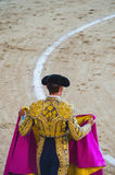 Torero holding his capote. A bullfighter holding his capote and awaiting for the bull in the bullring. Corrida de toros Stock Image