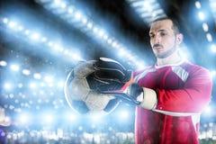 Torhüter hält den Ball im Stadion während eines Fußballspiels lizenzfreie stockfotos
