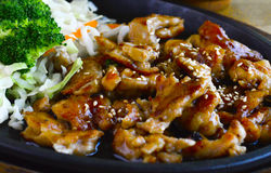 Tori Teriaki. This image is of teriyaki chicken with sesame seeds, white rice, broccoli, and vegetables on a skillet platter Royalty Free Stock Images