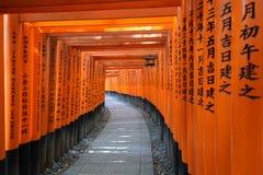 Torii在Fushimi Inari-taisha寺庙的隧道道路在京都,日本 免版税库存图片