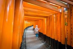 Torii门在Fushimi Inari祀奉与被弄脏的孩子,京都 库存图片