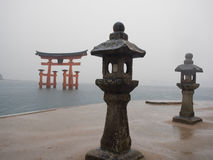 Torii Gate in the Ocean. A Torii Gate in Miyagima Island with a lantern holder in the foreground Stock Image