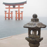 Torii Gate in the Ocean. A Torii Gate in Miyagima Island with a lantern holder in the foreground Royalty Free Stock Photography