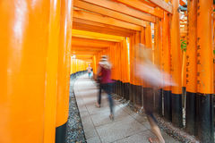 Torii gates in Fushimi Inari Shrine with blurred tourists, Kyoto Royalty Free Stock Photos