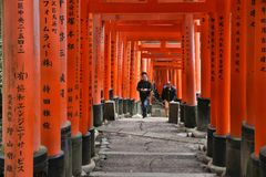 Torii gates. KYOTO, JAPAN - NOVEMBER 28, 2016: People walk along torii gates of Fushimi Inari Taisha shrine in Kyoto, Japan. There are more than 10,000 torii Royalty Free Stock Photo
