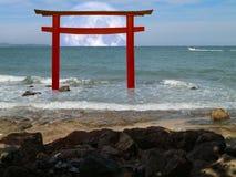 torii hölzerner japanischer Säulenstand über Seesonnenunterganghimmel Stockfotos