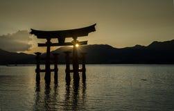 Torii - porta de flutuação da ilha de Miyajima (Itsukushima) no tempo do por do sol foto de stock royalty free