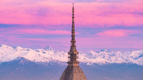 Torino Turin, Italy: cityscape at sunrise with details of the Mole Antonelliana towering over the city. Scenic colorful light on. The snowcapped Alps in the royalty free stock images