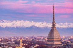 Torino Turin, Italy: cityscape at sunrise with details of the Mole Antonelliana towering over the city. Scenic colorful light on. The snowcapped Alps in the Stock Image