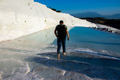Tourists enjoying in the termal water pools in Pamukkale. Torist walking in the slippery water pool warming his feet in thermal water Royalty Free Stock Photography