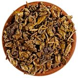 Torka grön tea i en lerakopp från över Royaltyfria Foton