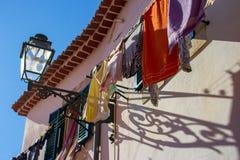 Torka kläder utanför hus med gatalyktan i Portugal Öppet fönster och torkalinne Traditionellt hushåll i Portugal royaltyfri foto