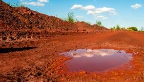 Torka röd jord med pöl i Kryvyi Rih, Ukraina Arkivfoton