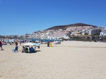 Torka sikten för den sandiga stranden av badningen och sammanträde för ferietillverkaresol i skugga under slags solskydd arkivfoto