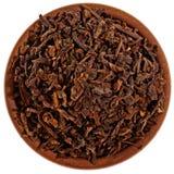 Torka svart tea i en lerakopp från över Royaltyfri Foto