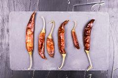 Torkad Cayenne chilipeppar på skärbräda på mörker texturerade bakgrund Arkivfoto