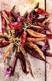 Torkad glödhet chilipeppar på mörk träbakgrund Royaltyfri Fotografi