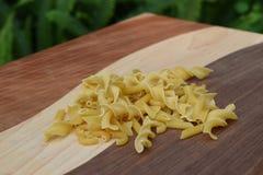 Torkad pasta på en handgjord wood skärbräda Royaltyfria Foton