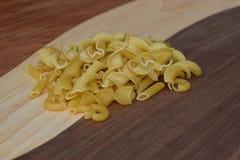 Torkad pasta på en handgjord wood skärbräda Royaltyfri Fotografi