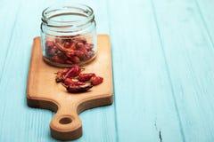 Torkad röd peppar på en skärbräda arkivbilder