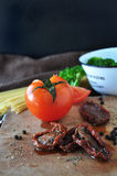 Torkad tomat och ny tomat på skärbräda Arkivfoton