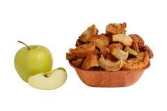 Torkade äpplen på en platta och en nya Apple Arkivbild