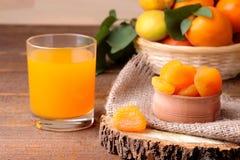 Torkade aprikors, aprikosfruktsaft och nya aprikors på en brun bakgrund Arkivbilder