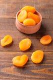 Torkade aprikors i en träbunkecloseup på en brun träbakgrund Fotografering för Bildbyråer