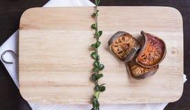 Torkade balefruit och örter på skärbrädaträbakgrund fl Arkivfoton