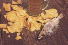 Torkade fisk, öl och chiper Arkivbilder