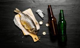 Torkade fisk och ölflaskor på svart bräde Royaltyfri Bild