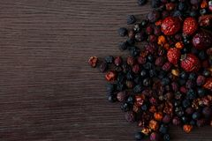 Torkade frukter på sikt för tabell för mörk brunt träbästa med kopieringsutrymme Rosa bär för hund och torkad vinbärsvartcloseup Royaltyfri Bild
