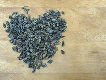 Torkade gröna teblad läggas ut på den grova träyttersidan av beiga i formen av en hjärta Arkivbild