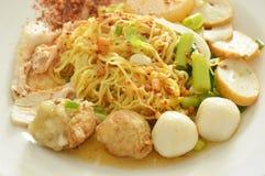 Torkade kryddiga kinesgulingnudlar som överträffar fisk- och räkabollen med skivan, kokade griskött på plattan Royaltyfri Bild