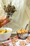 Torkade kvistar av rosmarin i en krus Kryddigt gräs smaktillsats I händerna av en ung kvinna royaltyfri fotografi