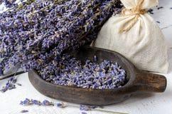 Torkade lavendelgrupp och lavendelblommor i träbunke royaltyfri foto