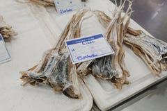 Torkade lisa fiskar på fiskmarknaden med prisbrädet i portugisiskt språk royaltyfria foton