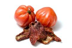 Torkade och nya tomater på vit Arkivfoton