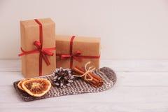 Torkade orange och kanelbruna pinnar på handske spelrum med lampa Julfilial och klockor Royaltyfri Fotografi