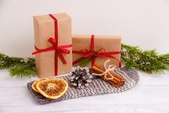 Torkade orange och kanelbruna pinnar på handske spelrum med lampa Julfilial och klockor Arkivbild