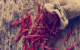 Torkade peppar för röd chili i säck med på gammal träbakgrund, tappningfärgsignal Arkivbild