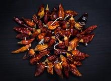 Torkade peppar för röd chili på en rad, svart bakgrund Arkivbild