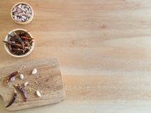 Torkade peppar och vitlök för röd chili på träbräde Fotografering för Bildbyråer