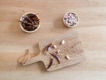Torkade peppar och vitlök för röd chili på träbräde Arkivbild