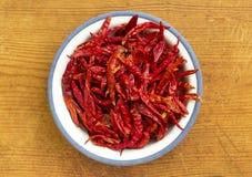 Torkade röda chili i platta på träbakgrund arkivbild