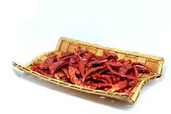 Torkade röda chilies, varm röd peppar i den wood korgisolaten på vit bakgrund Royaltyfria Foton